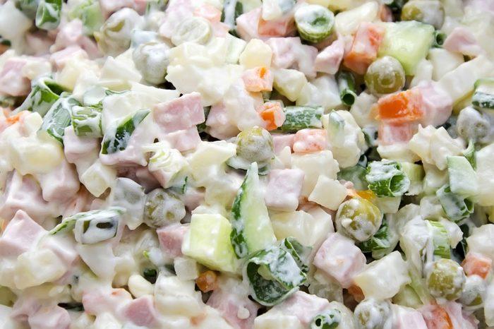 Food background - salad olivier close-up. Green peas, cucumber, potatoes, sausage, mayonnaise