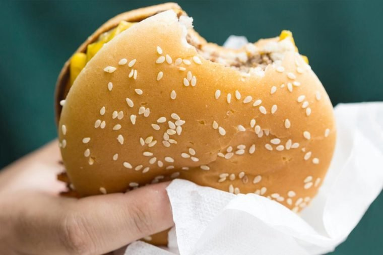 A fast food cheeseburger with a bite taken out of it / one bite taken out of it / Bitten hamburger.