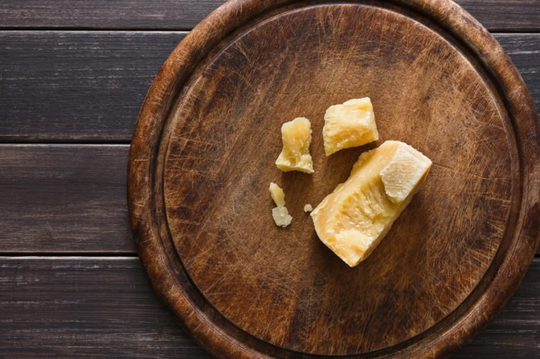 Cheese delikatessen pieces on rustic wood. Wooden desk with parmesan cuts, top view image with copy space