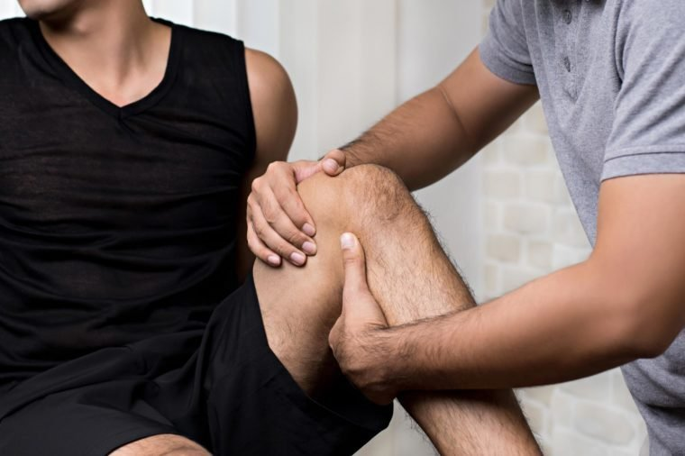 Therapist treating injured knee of athlete male patient in clinic - sport physical therapy concept,panoramic banner