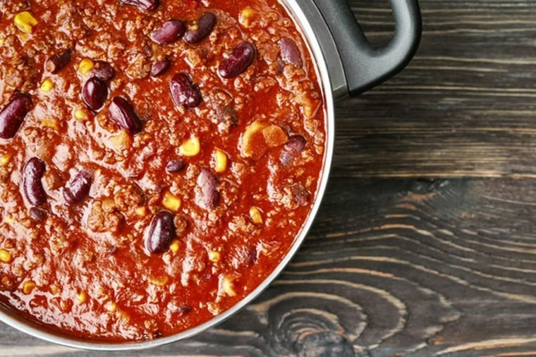 Saucepan with delicious chili con carne on wooden background