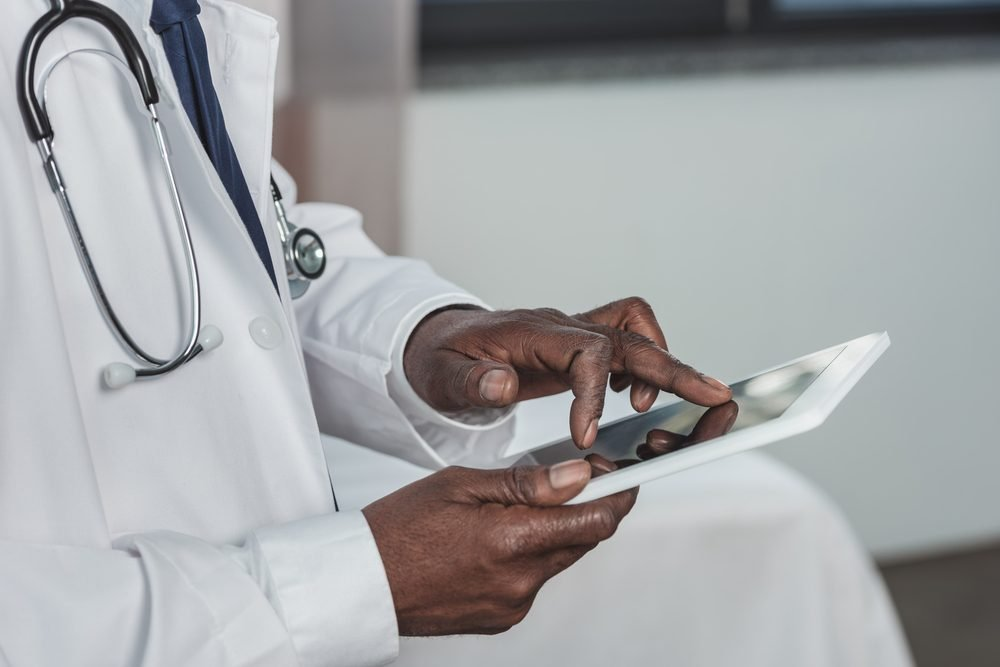 Cropped image of african american doctor searching something on a tablet