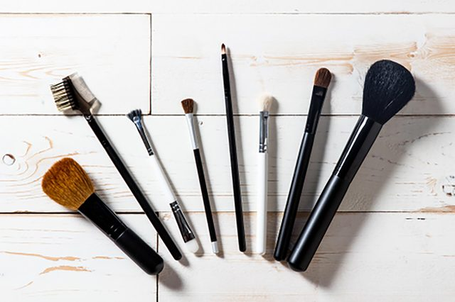 Long panorama for display of professional makeup accessories with blush and eyeshadow brushes, white wooden background, copy space, top view