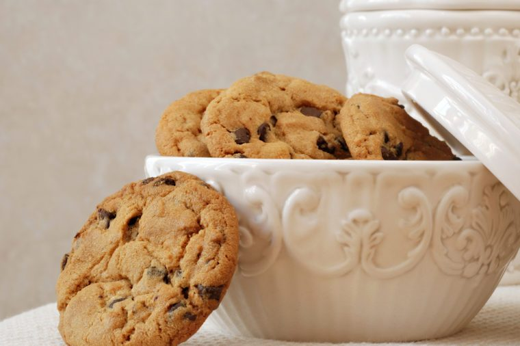 Freshly baked, chocolate chip cookies in a vintage dish with matching cookie jar in the background. Close-up with shallow dof.