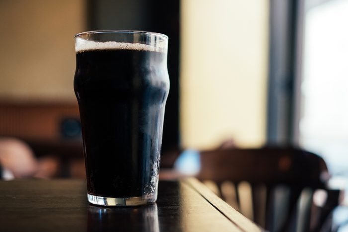 Pint of stout beer on wooden table in the bar