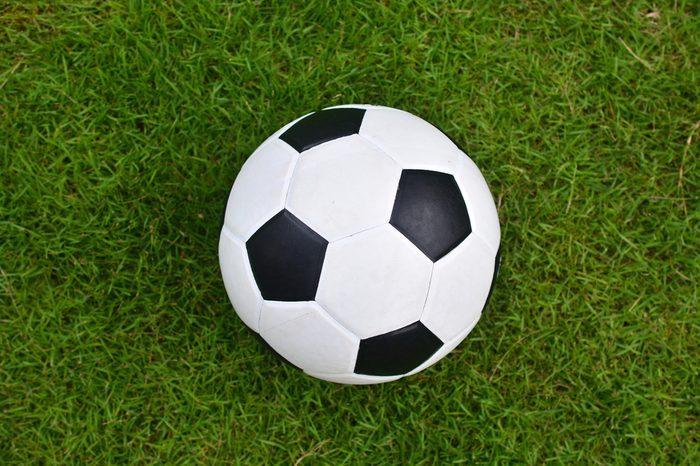 Soccer football on green grass field, Top view