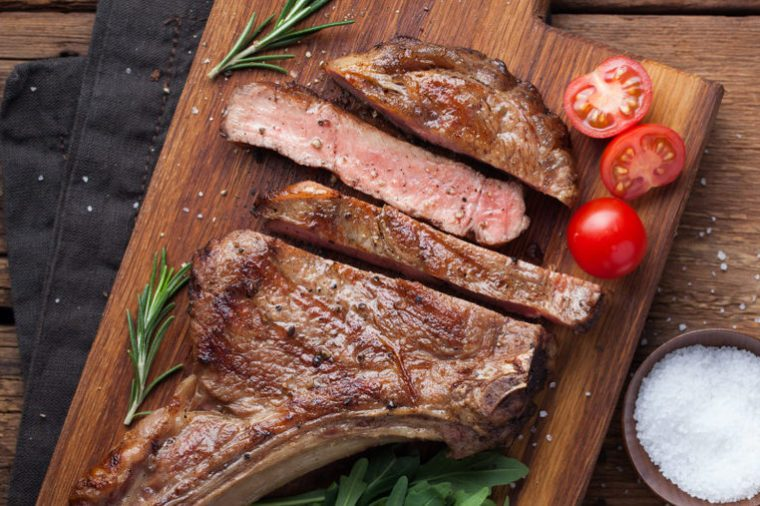 Grilled cowboy beef steak, herbs and spices on a rustic wooden background. Top view with copy space for your text.