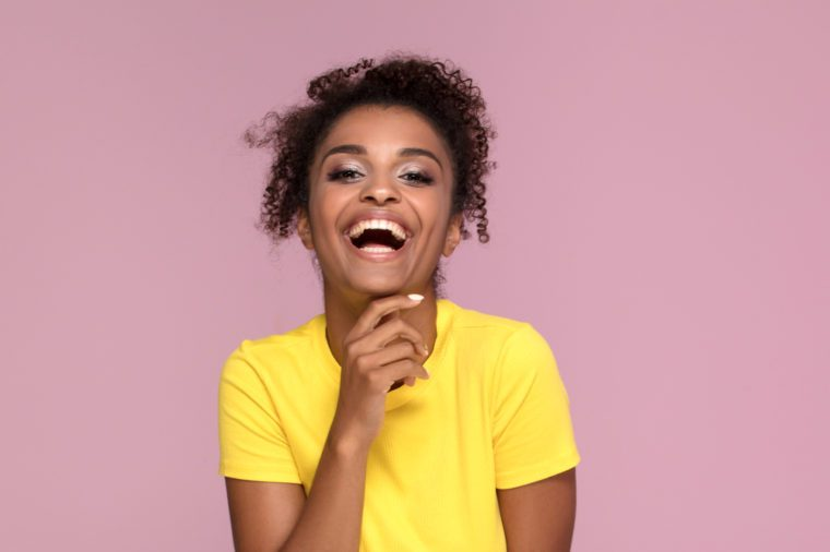 Excited african american woman smiling, looking at camera, posing on pink pastel background.