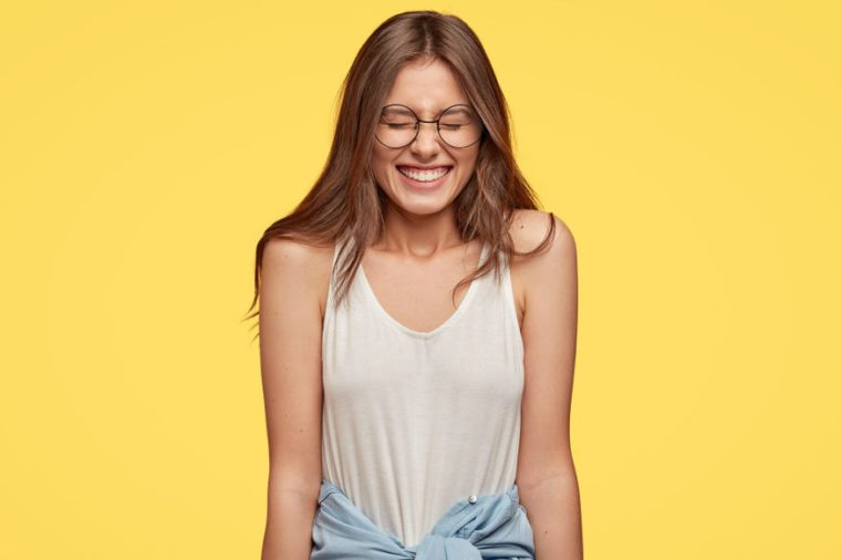 Funny emotive teenager with overjoyed expression, closes eyes from pleasure, laughs at good joke, dressed in casual outfit, isolated over yellow background. People and positive emotions concept