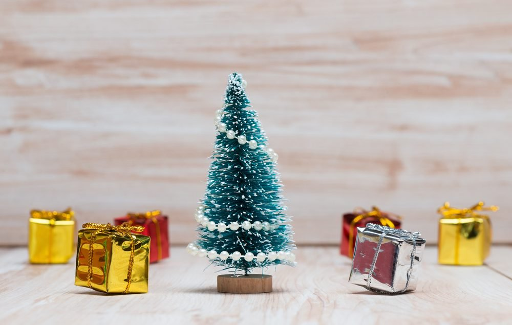 little Christmas tree and gifts on wooden background
