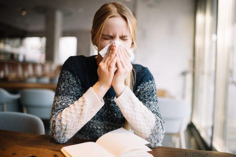 Young blonde woman feeling bad, using handkerchief. Allergy. Sickness. Infection. Virus. Flu.