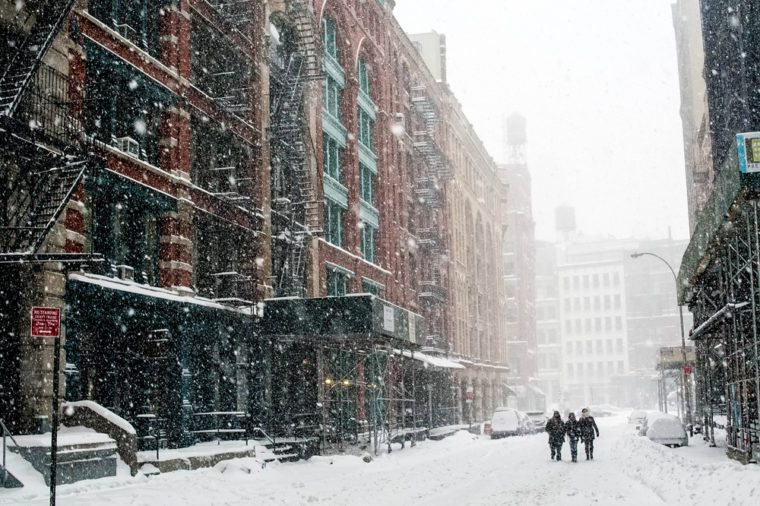 Friends travel down a New York City street in a blizzard