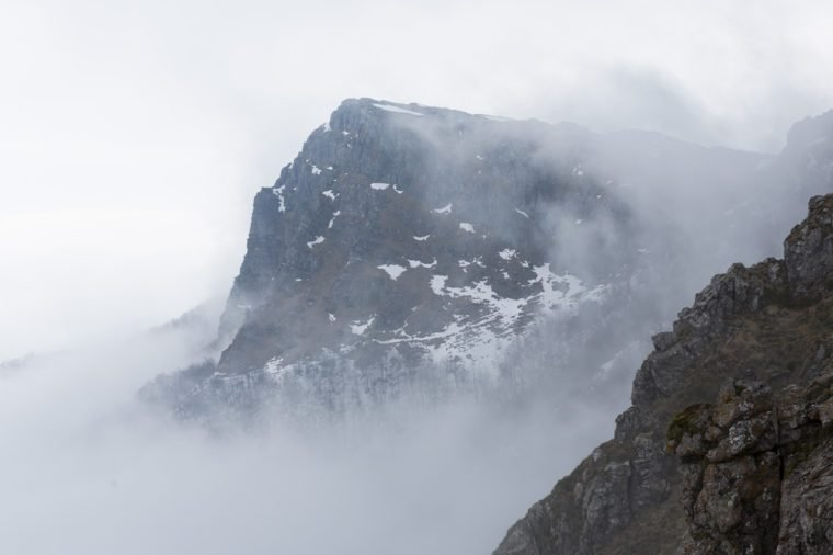 High rocky mountain peak covered with snow and fog.