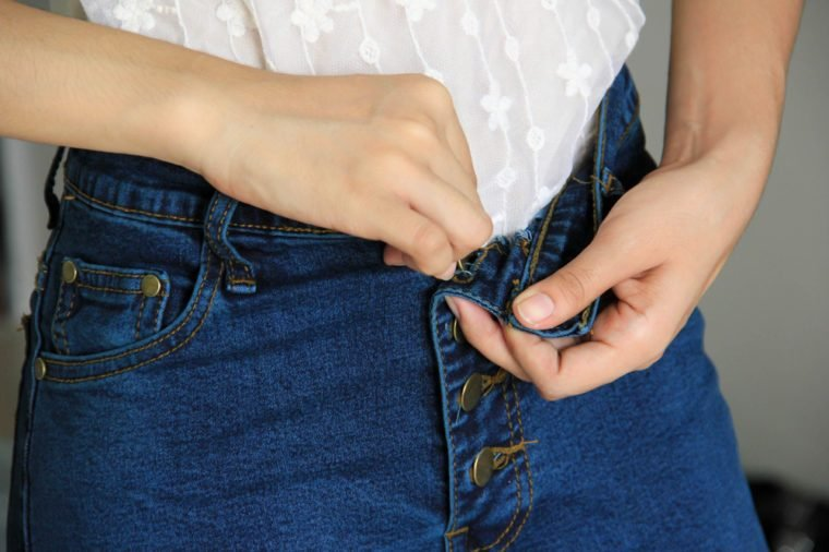 woman getting dressed wearing jeans