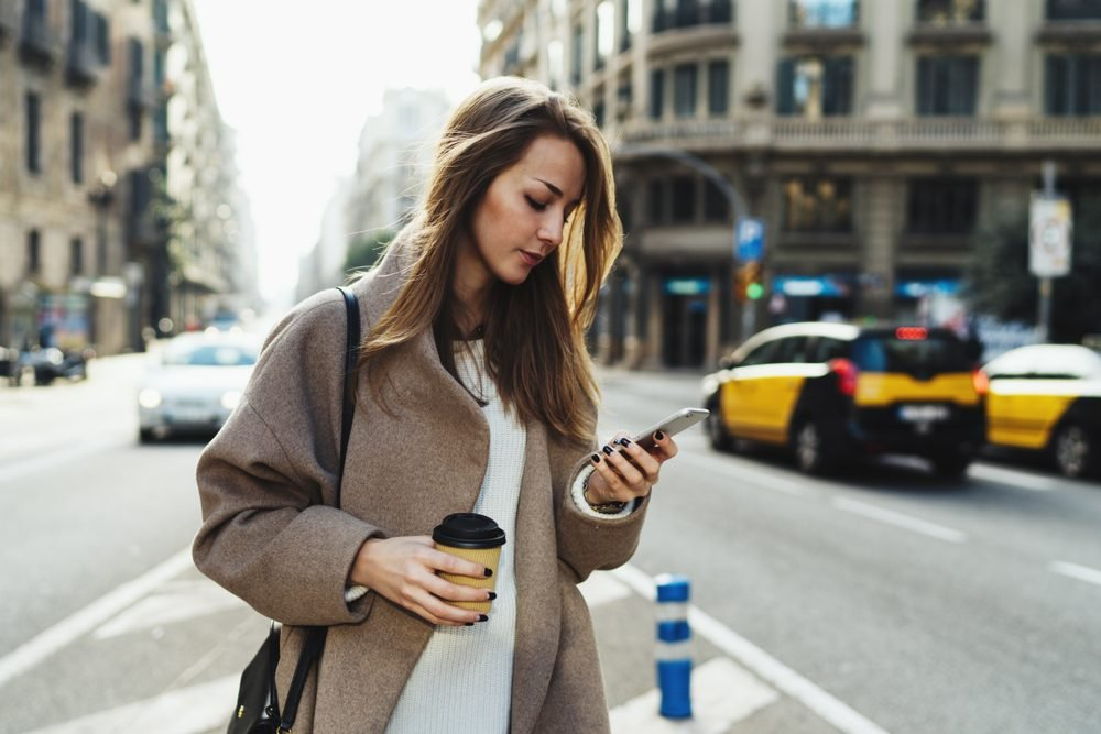 Travel blogger using route application on the mobile phone to find the needed address in a city. Young stylish blonde woman reading emails on the smartphone while passing by with a take away coffee