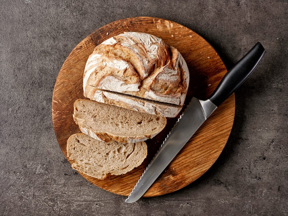 freshly baked bread and knife on dark gray table, top view