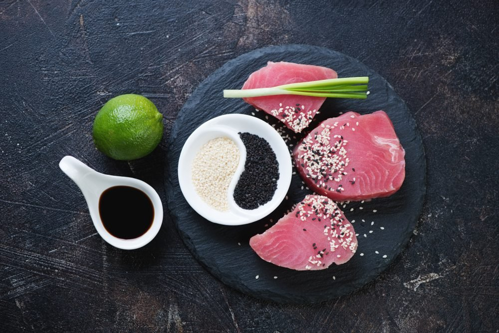 Stone slate tray with raw fresh tuna steaks and condiments, above view on a dark brown stone background, horizontal shot