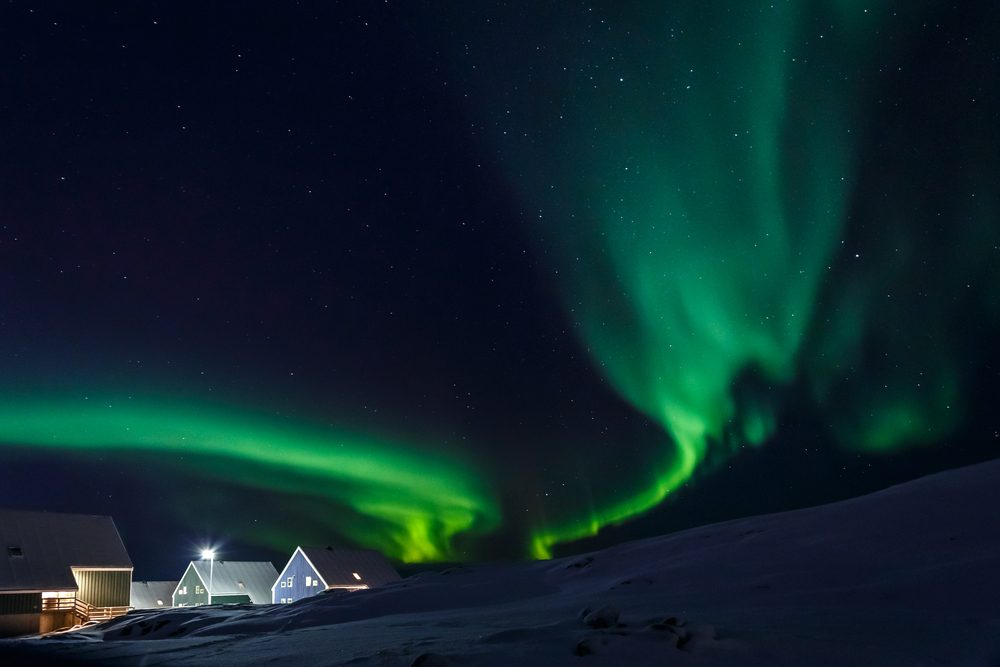 Arctic village and green waves of Northern lights in a suburb of Nuuk, Greenland