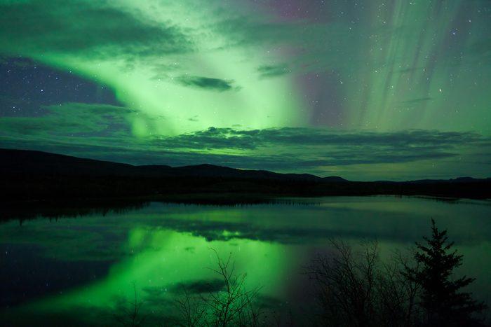 Night Sky Stars, clouds and Northern Lights mirrored on calm lake in Yukon, Territory, Canada.