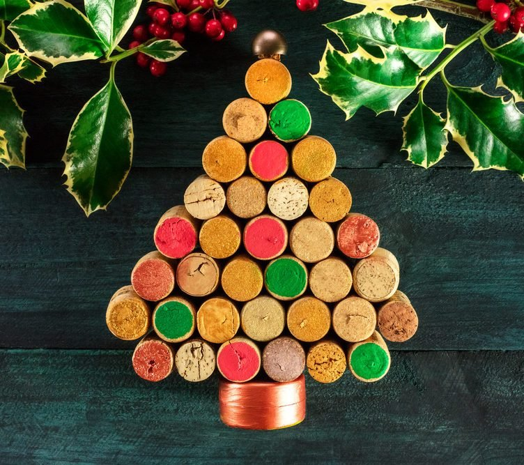 A photo of a handmade Christmas tree made up of painted wine corks. Winemaker's Christmas concept. On a dark background with holly branches and a place for text