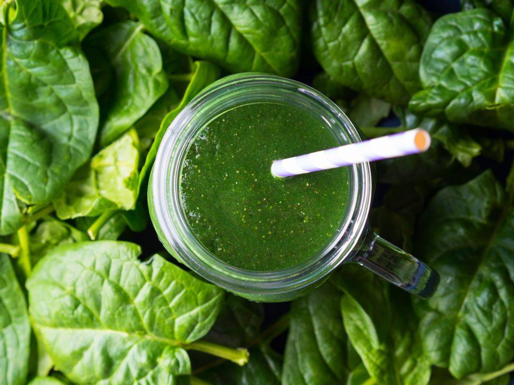 Green spinach spirulina smoothie in mason jar on blue background