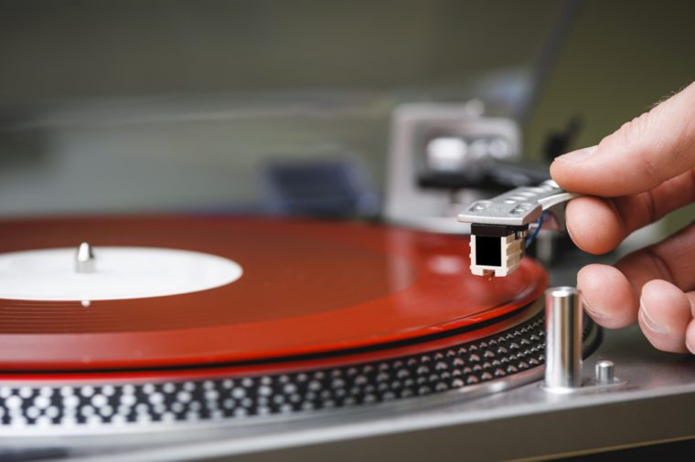 a person placing the needle on a record.