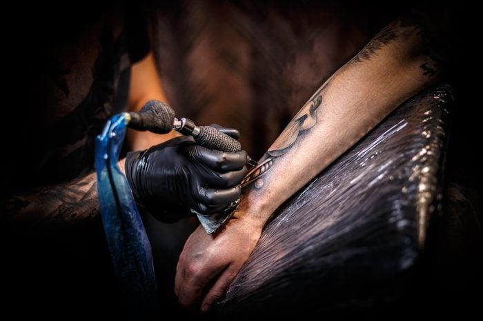 Tattoo artist creating a tattoo on a man's arm.