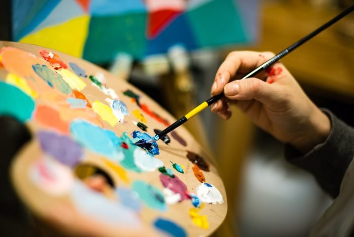 artist painting with acrylic colors and mixing tones on the pallet. blur background abstract photo