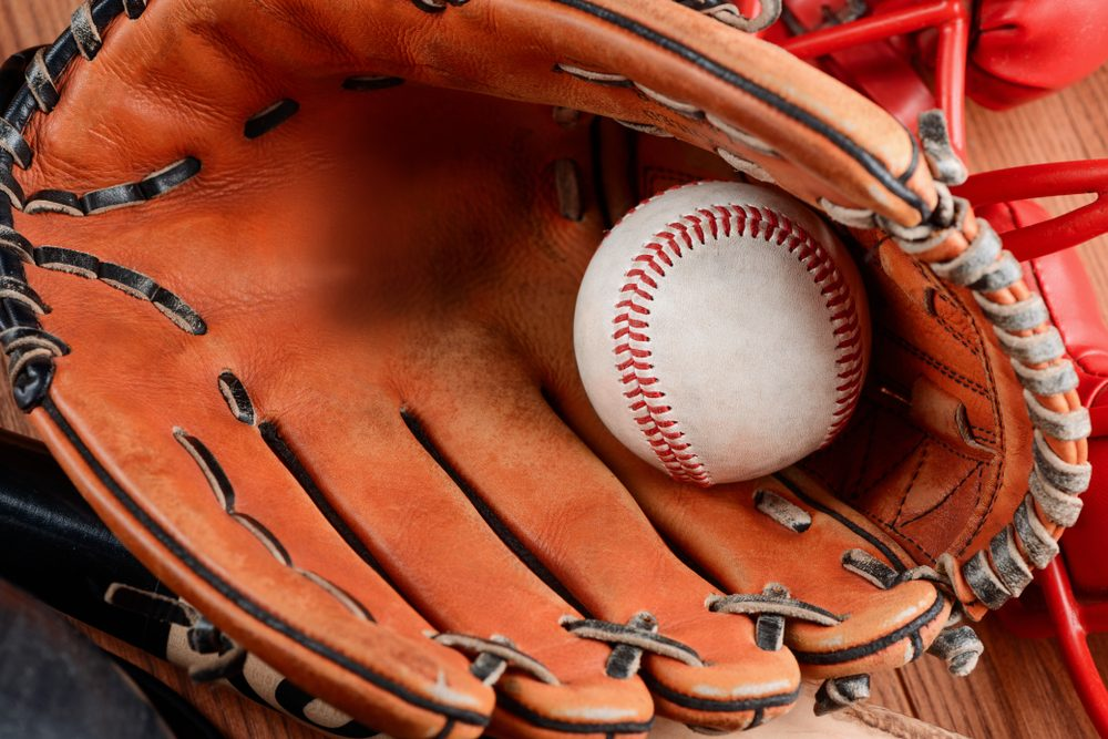 Detailed view on leather mitt glove and ball. Baseball equipment for catching a pitch.