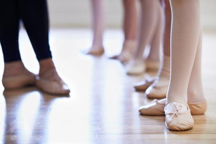 Close Up Of Teacher And Children's Feet In Ballet Dancing Class
