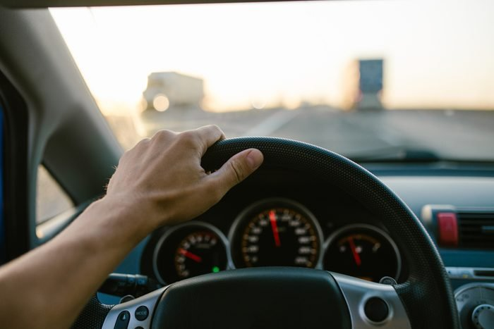 Selective focus man's hand on steering wheel, driving a car at sunset. Travel background