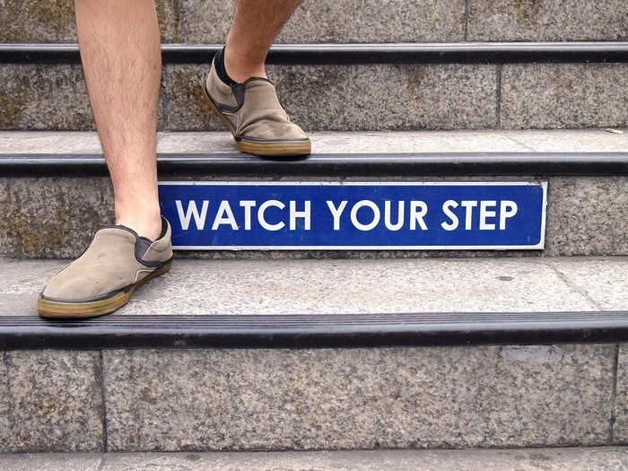 Photo of Watch your step sign on a staircase and a pair of feet with shoes