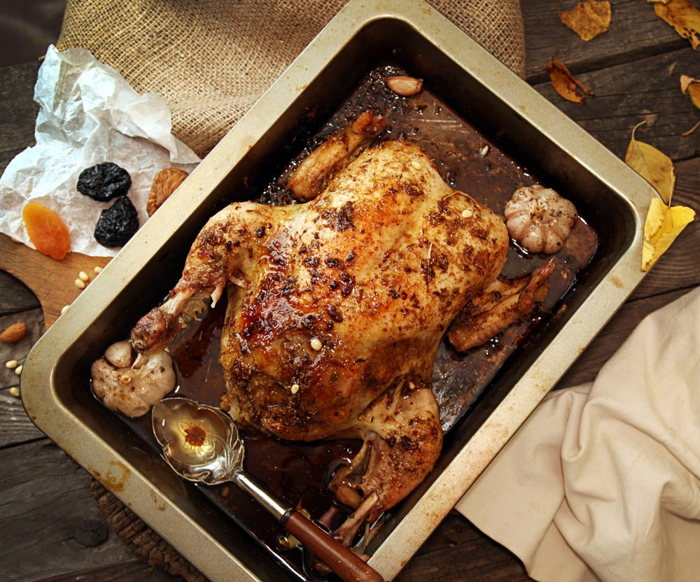 Roasted small turkey for celebration Christmas in roasting pan on old rustic wooden table. Stuffed with couscous with a fig, prunes, dried apricots, almonds and pine nuts