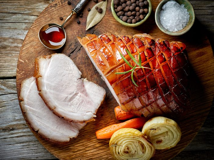 roasted pork slices on rustic wooden table, top view