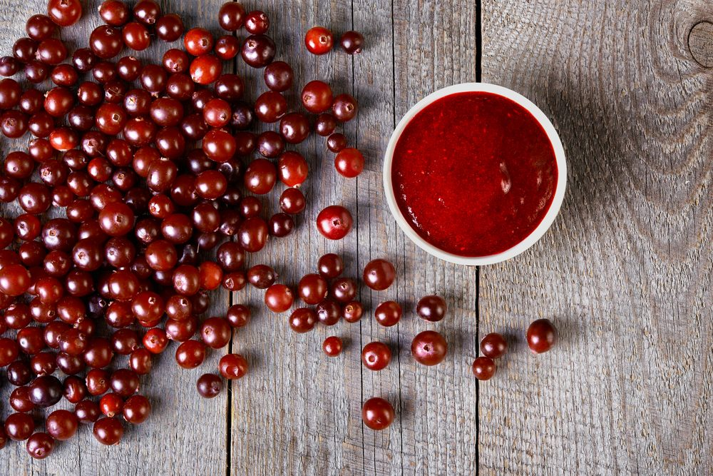 cranberry sauce and scattered berries on wooden table. top view