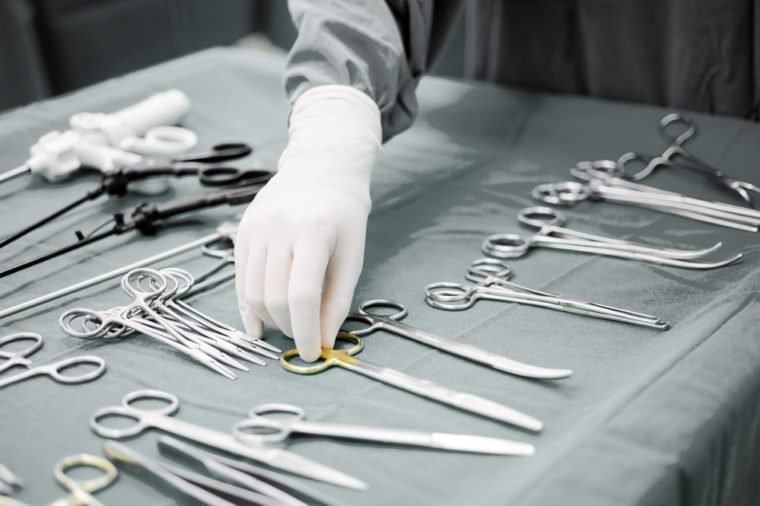 Detail shot of steralized surgery instruments with a hand grabbing a tool ,selective color technique