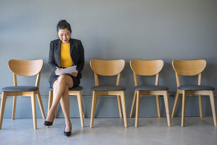 A woman sitting in a chair reading a document while waiting for a job interview in the waiting room.