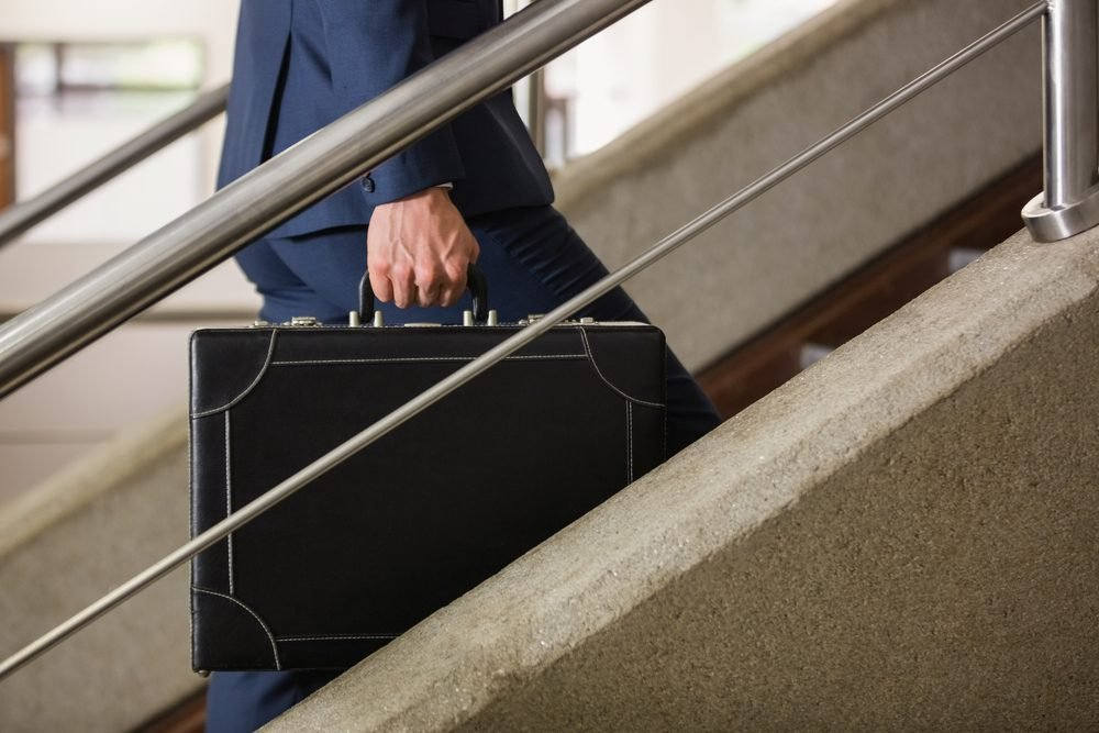 Businessman climbing up the stairs in office building