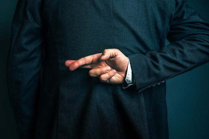 Dishonest businessman telling lies, lying male entrepreneur holding fingers crossed behind his back