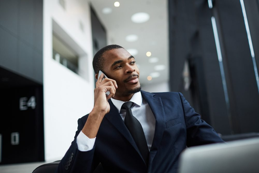 Confident young businessman of African-american ethnicity speaking by smartphone at work