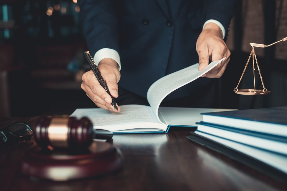 Justice and law concept. Gavel on sounding block in hand's Male judge at a courtroom, working with document law books, report the case on table in modern office.