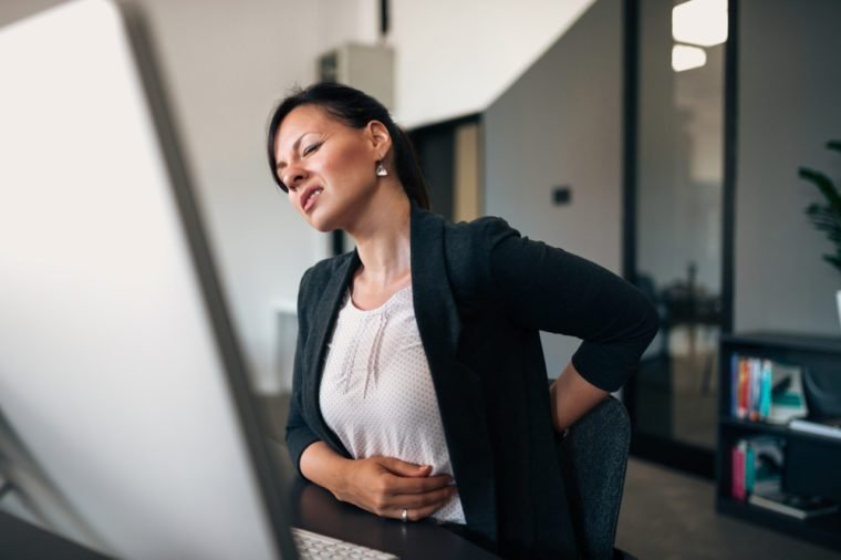 Beautiful young businesswoman having back pain while sitting at office desk.
