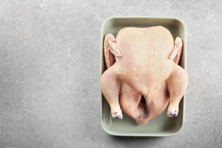 Whole raw turkey in casserole on grey background