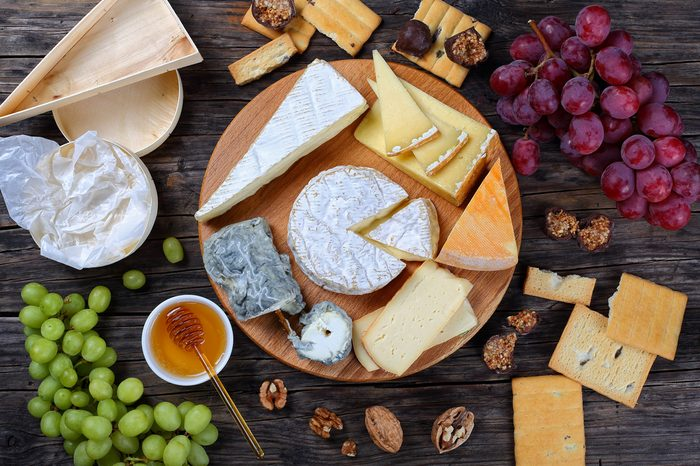 set of authentic french Cheese plate served with grapes, honey, homemade chocolate sweets and nuts on wooden round board on dark background, view from above