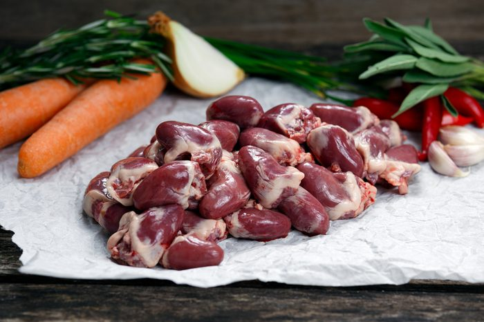 Raw Duck hearts on crumpled paper, decorated with greens and vegetables. on old wooden table.
