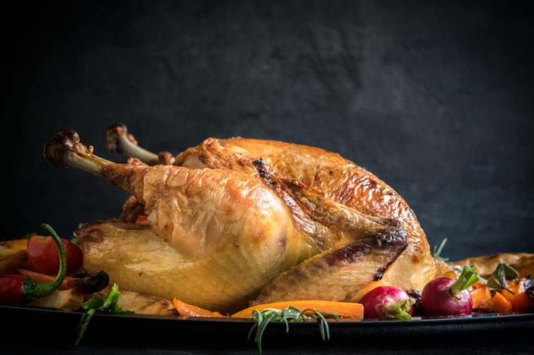 Served small split roasted turkey stuffed with vegetables on dark background