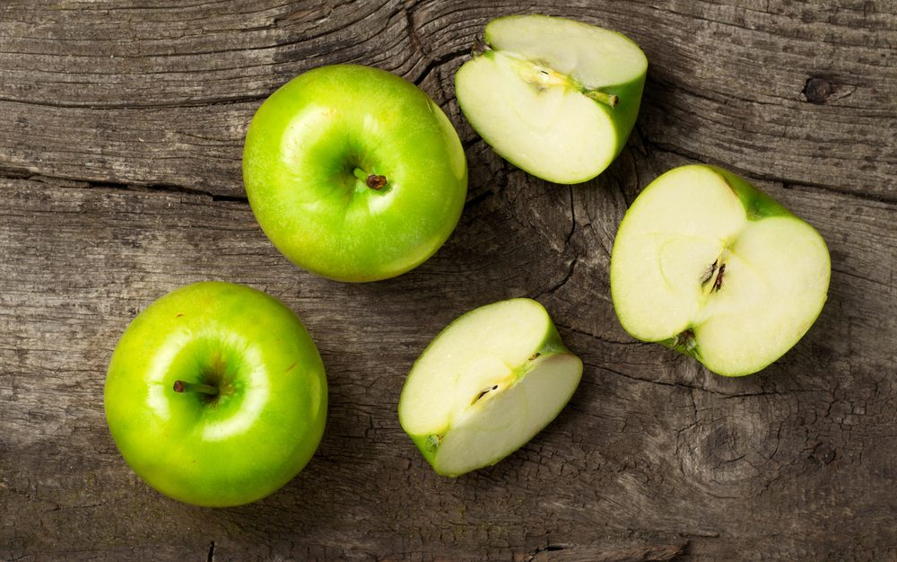 ripe green apples and apple slices on wooden gray background, top view