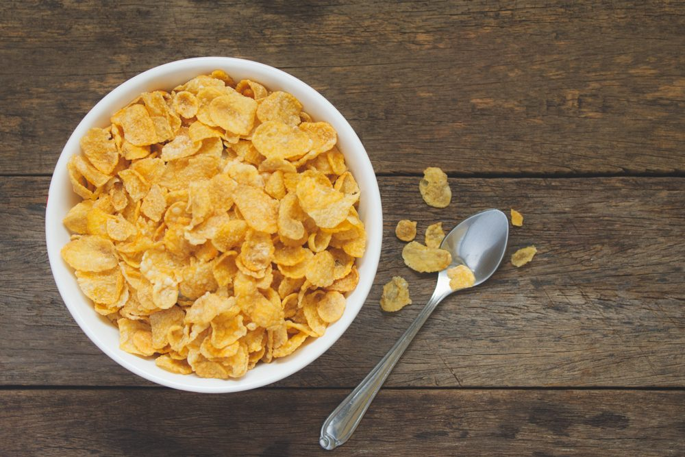 bowl of cereal on wooden table, overhead view.