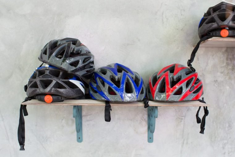 Stack of bicycle helmets on wooden shelf and grange cement wall.
