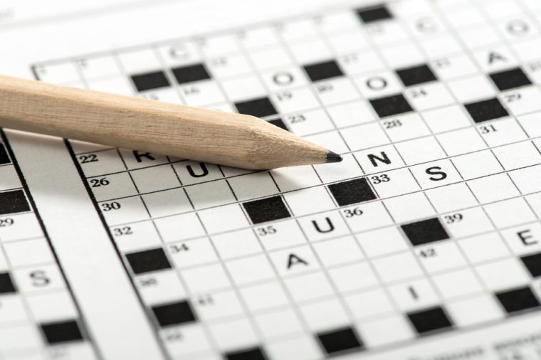 Conceptual Sharpened Pencil on Top of Crossword Puzzle Game Paper in Close up Shot